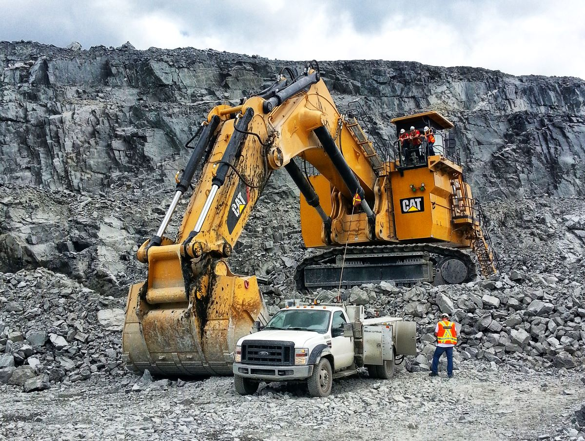 A Large CAT Excavator with a Ford Truck and a Person for scale